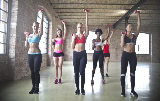 Plusieurs jeunes femmes font du sport en groupe dans une salle de gym