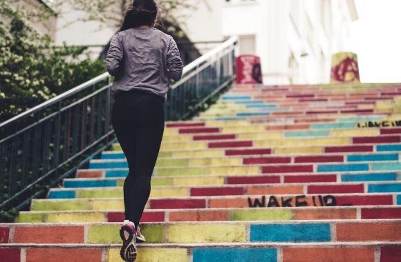 Une femme est en train de monter un escalier en courant