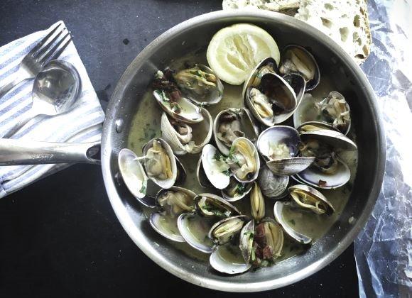 Des fruits de mer mis à côté d'une fourchette et d'une cuillère après avoir été bouillis