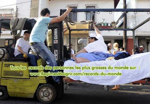 On soulève le lit de Manuel Uribe pour le mettre sur un camion
