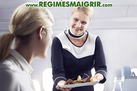 Une hôtesse de l'air donne un plateau repas à une voyageuse