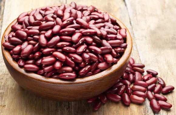Les haricots rouges entassés dans un bol et posé sur une table en bois