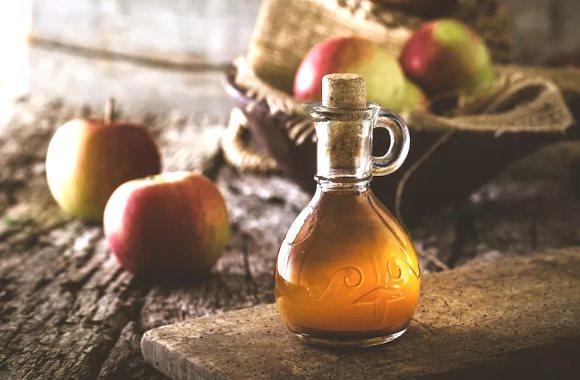 Une bouteille de vinaigre de cidre est posée sur une table en bois à côté de plusieurs pommes