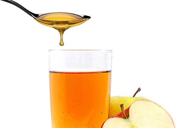 Une cuillère contenant du vinaigre de cidre est versée dans un verre contenant le même liquide